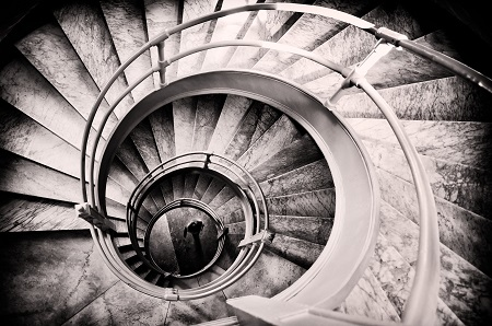 A staircase descending into a downward spiral towards darkness