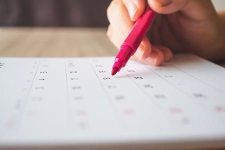 Hand with a pen writing on calendar. Credit: https://www.istockphoto.com/au/portfolio/kwangmoozaa