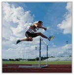 man jumping over hurdle