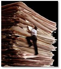 man climbing mountain of paper work
