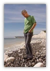 man walking over pebbles on a beach